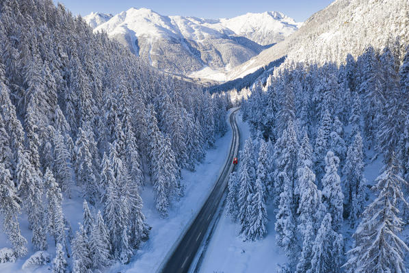 Car traveling on icy road framed by fir trees forest covered with snow in winter, aerial view, Switzerland