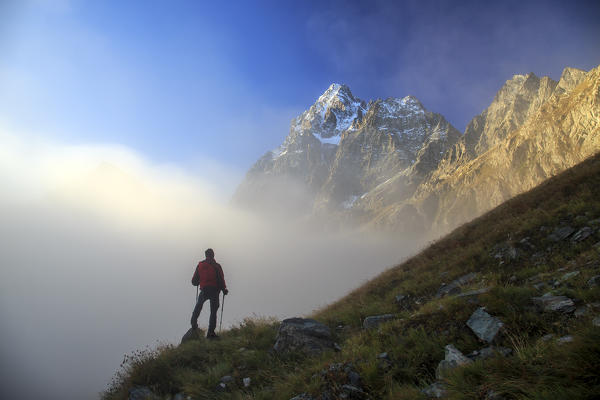 Hiker watching the clouds that rise from the valley and hide Monviso. Cozian Alps, Piedmont, Italy Europe