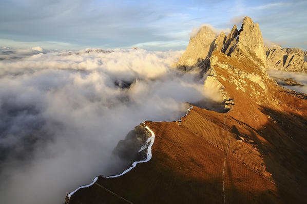 Aerial shot from Seceda of Odle surrounded by clouds at sunset. Dolomites Funes Valley Trentino Alto Adige South Tyrol Italy Europe