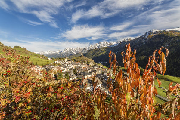 Autumn colors frame the village of Ardez surrounded by woods and snowy peaks Engadine Canton of Graubünden Switzerland Europe