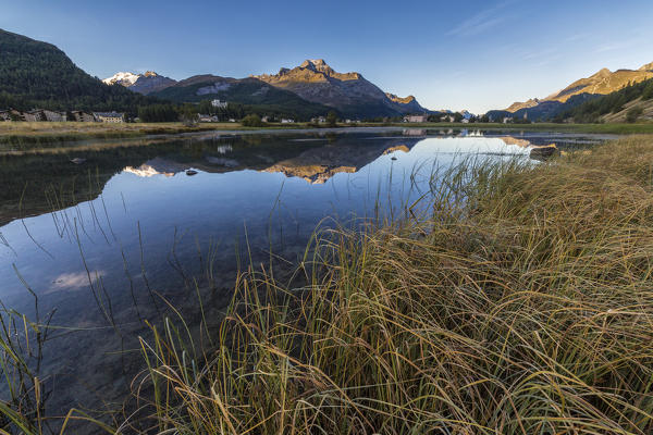 Dawn illuminates the autumn landscape and Lake Sils Engadine Canton of Graubünden Switzerland Europe