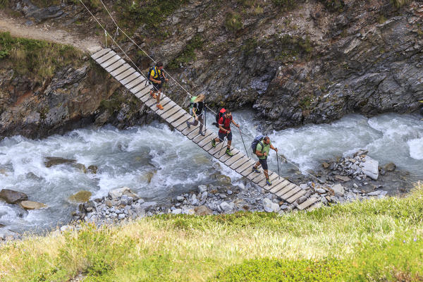 Hikers cross the wooden bridge on a creek Minor Valley High Valtellina Livigno Lombardy Italy Europe