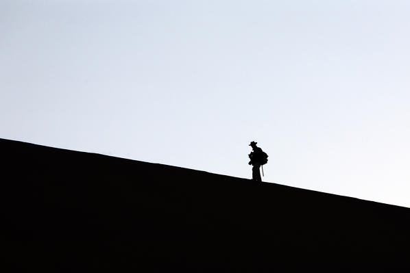 Profile of a hiker on the sand dune shaped by the wind Deadvlei Sossusvlei Namib Desert Naukluft National Park Namibia Africa