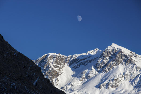 The moon appears above the snowy peaks in the blue sky Julierpass Albula District Canton of Graubünden Switzerland Europe