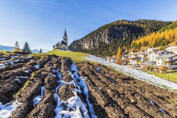 The church of Schmitten surrounded by colorful woods and snow Albula District Canton of Graubünden Switzerland Europe
