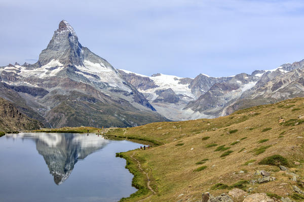 Hikers on the trail to the Matterhorn reflected in Lake Stellisee Zermatt Pennine Alps Canton of Valais Switzerland Europe