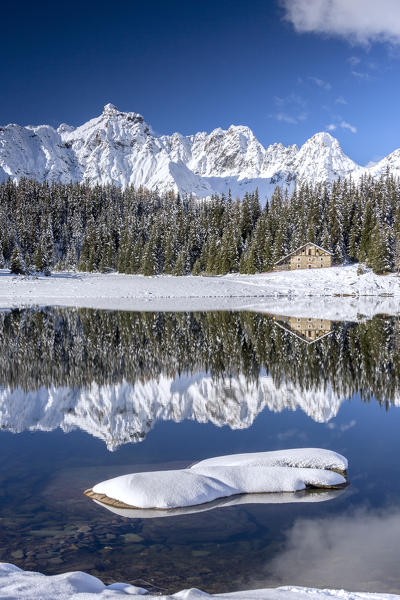 Wooden chalet surrounded by snowy peaks and woods reflected in Palù Lake Malenco Valley Valtellina Lombardy Italy Europe
