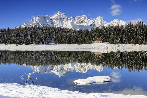 Hiker jumps on the shore of 