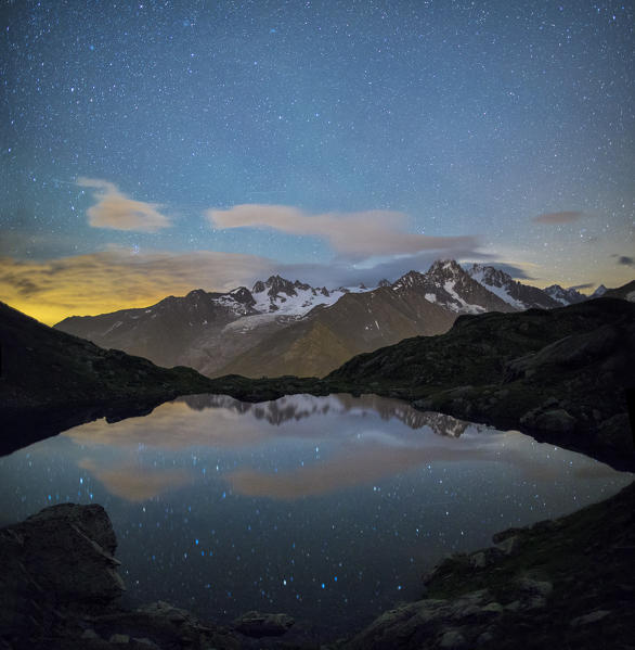 The stars illuminate the snowy peaks and reflected in Lac de Cheserys Chamonix Haute Savoie France Europe
