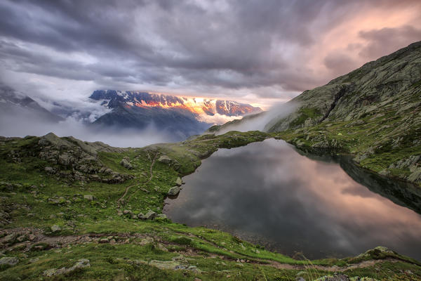 Clouds are tinged with purple at sunset at Lac de Cheserys  Chamonix Haute Savoie France Europe