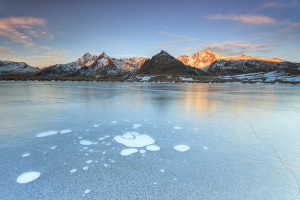 Ice bubbles on the frozen surface of Andossi Lake at sunrise Spluga Valley Valtellina Lombardy Italy Europe