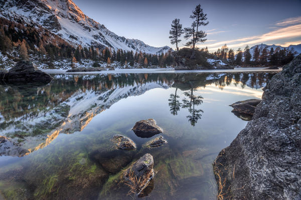 Autumn reflections at Saoseo Lake still partially frozen Poschiavo Valley Canton of Graubuenden Switzerland Europe