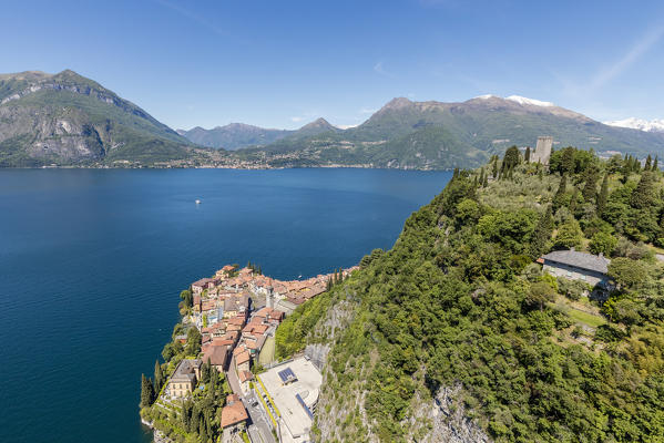 Aerial view of the green hill and castle overlooking Varenna surrounded by Lake Como Lecco Province Lombardy Italy Europe
