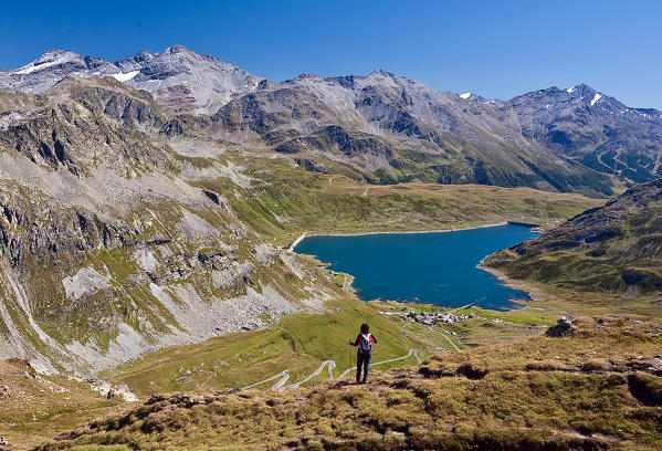 Hikers observe the landscape overlooking the reservoir of Montespluga and on the tops of Valchiavenna. Vallespluga. Lombardy. Italy. Europe.