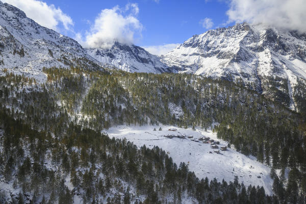 Aerial view of the alpine village of Laguzzola framed by woods and snowy peaks Spluga Valley Valtellina Lombardy Italy Europe