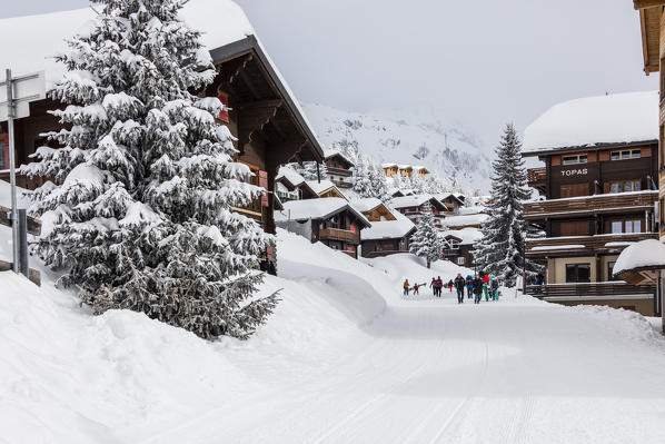 Tourists in the alpine village surrounded by snow and woods Bettmeralp district of Raron canton of Valais Switzerland Europe