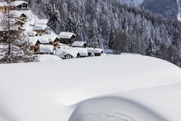 The snowy woods frame the typical mountain huts Bettmeralp district of Raron canton of Valais Switzerland Europe