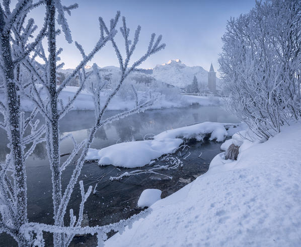The frost and snow on tree branches frame the river Inn at dawn Sils Canton of Graubunden Engadine Switzerland Europe