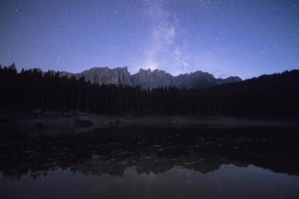Stars on the peaks of Latemar mountain range reflected in Lake Carezza Ega Valley Province of Bolzano South Tyrol Italy Europe