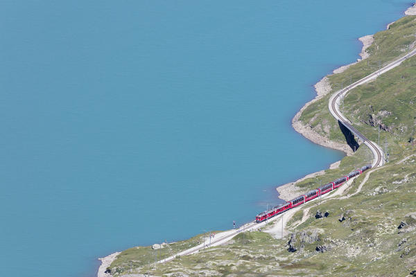 The Bernina Express train passes on the shores of Lago Bianco Bernina Pass Canton of Graubünden Engadine Switzerland Europe