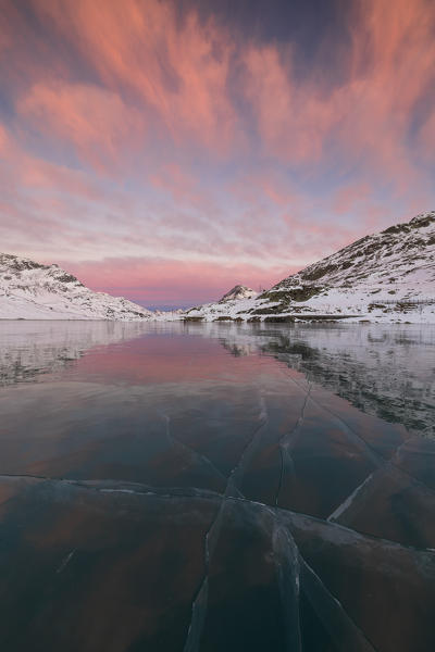 The frozen Lago Bianco framed by pink clouds at dawn Bernina Pass canton of Graubünden Engadine Switzerland Europe