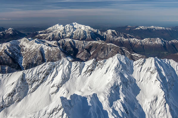 Flying high above the Orobie Alps after a heavy snowfall. In the background the two Grigne, in the foreground the peaks of Lesina valley Valtellina, Sondrio, Lombardy, Italy. Europe