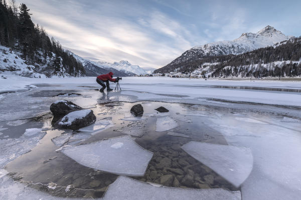 Photographer at dawn on frozen Lake Champfer, Silvaplana, Maloja Region, canton of Graubunden, Engadin, Switzerland