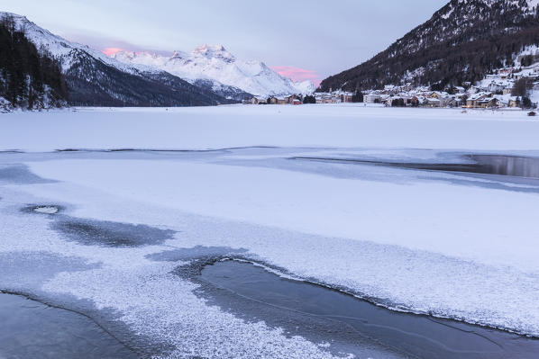 Village of Silvaplana and Piz Da La Margna seen from icy Lake Champfer, St.Moritz, canton of Graubunden, Engadin, Switzerland