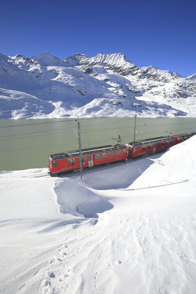 The Bernina Express (Unesco World Heritage) at the Bernina pass close to Lake Bianco - Bernina pass, Engadin, Canton Graubuenden, Switzerland Europe