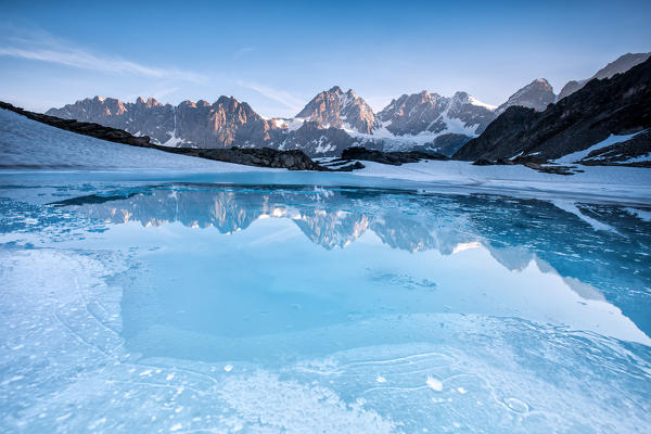 The reflection of the Bernina range in the icy water of little lake Forbici while melting - Alps, Valmalenco, Valtellina Sondrio, Lombardy, Italy Europe