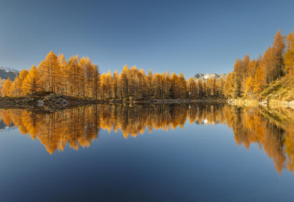 Autumn reflections on Azzurro lake, Motta, Campodolcino, Sondrio province, Lombardy, Italy, Europe