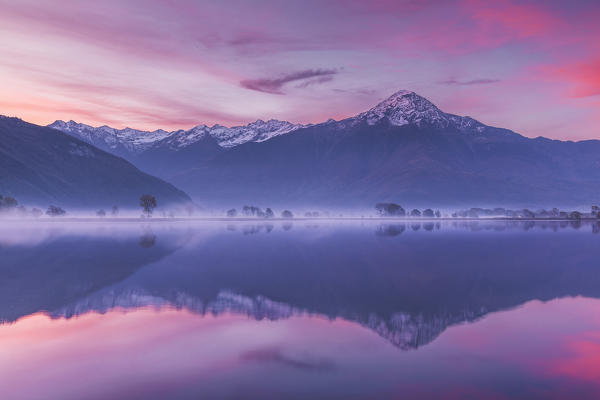 Sunrise on Legnone mount (Lecco province) reflected into Mera river from Dascio village, Sorico, Riserva Naturale Pian di Spagna e Lago di Mezzola, lake Como, Como province, Lombardy, Italy, Europe