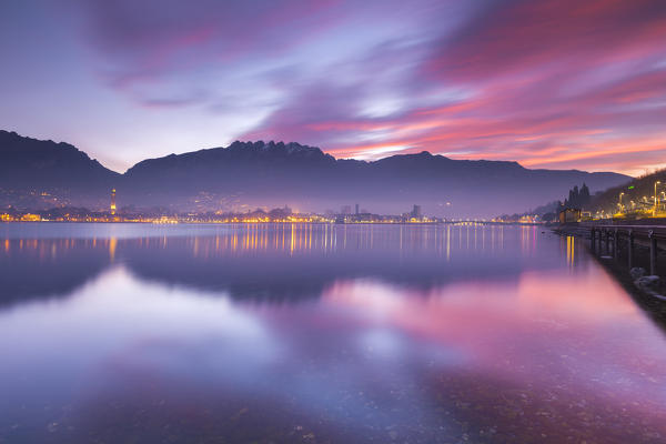 Lights of Lecco and mountains during a fiery sunrise, Lecco, lake Como, Lombardy, Italy, Europe
