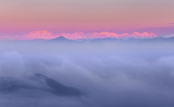 Rosa Mount and other peaks from alps rise up from a sea of clouds at sunrise. View from Brunate town (Como province, Lombardy, Italy, Europe)