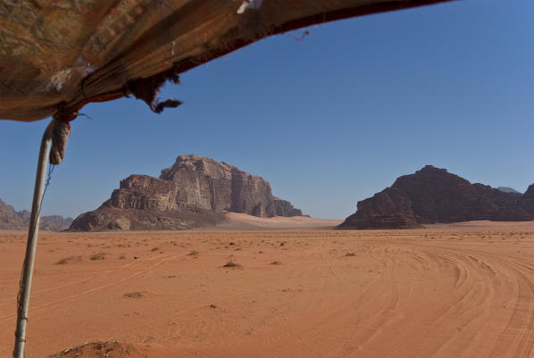 Mount Rum on the left is made up of granite rock and rises from the red sand of Wadi Rum desert, Jordan
