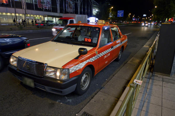 A taxi with the right guidance in the night of the Japanese metropolis. Tokyo, Japan