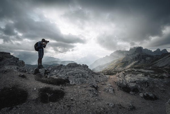 A photographer taking pictures into Dolomites. Lavaredo Three peaks, Bolzano province, South Tyrol, Italy.